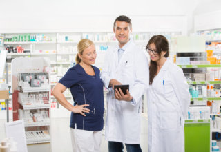 Portrait of confident pharmacist using digital tablet with coworkers in pharmacy